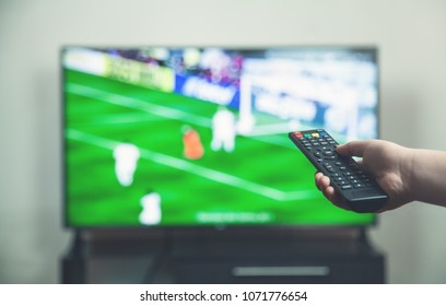 Watching football match on tv with remote controller.