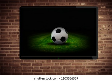 Watching football on tv. A flatscreen on the wall shows a football match.
