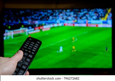 Watching Football on TV and using remote controller.