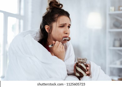 Watching melodrama. Woman feeling emotional while watching melodrama and eating chocolate spread with spoon