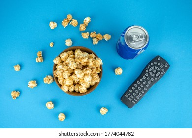 watching movie at home concept, cold refreshing blue pepsi can, wooden bowl of fresh caramel popcorn, remote tv control, top view