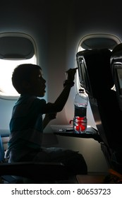 Watching a movie on the airplane - Silhouette of a little boy watching a movie on the airplane