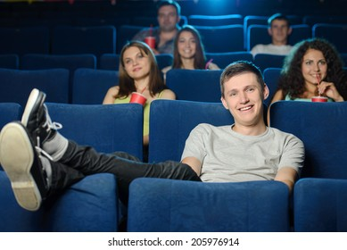 Watching a movie. Young men holding his feet on the seat while watching movie at cinema
