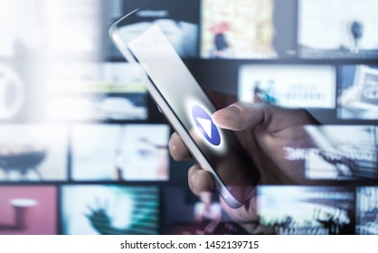 Watching movies and series with smartphone. On demand (VOD) service. Future multimedia technology in mobile phone. Man pressing play button. Entertainment of tv network. Many online video thumbnails.