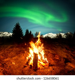 Watching the Northern lights sat by a warm camp fire!