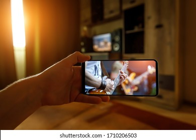 Watching online music concert at home using a mobile phone. Guitar close-up on the screen - Shutterstock ID 1710206503