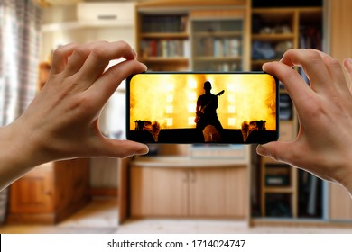 Watching online music concert at home using a mobile phone. Guitarist silhouette on the screen