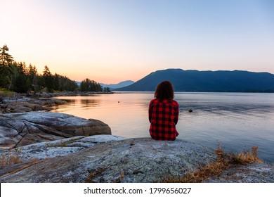Watching a Peaceful Sunrise on the Ocean Coast. Located in Saltery Bay, Sunshine Coast, British Columbia, Canada.