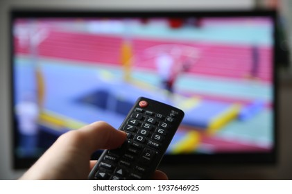 Watching pole vault on TV. Finger on the Volume up button on the remote. (Focus on the remote)