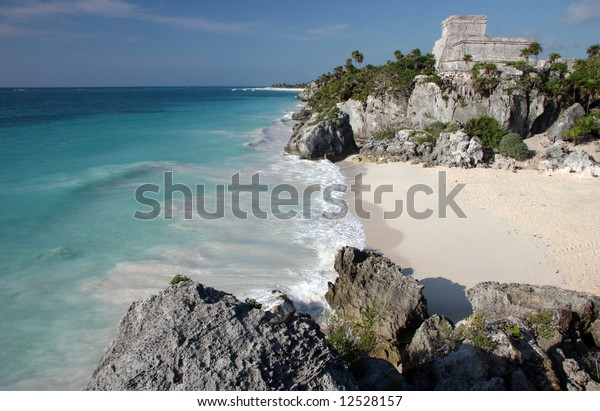 Watching the sandy beach and Tulum ruins from a rock. Tulum. Yucatan. Mexico