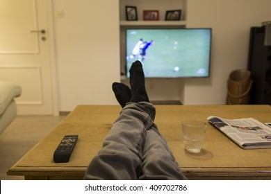 Watching a soccer match on TV with the feet on the table.