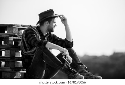 Watching sunset. Farmer cowboy handsome man relaxing after hard working day at ranch. Romanticism western culture. Farmer in hat sit relax. Evening time. Farmer drink alcohol enjoy view from his farm.