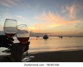 Watching the sunset while two hands are holding two glasses of wine at a tropical beach on Mauritius Island during a romantic holiday