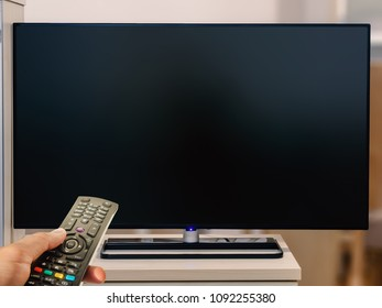 watching television with remote control at home. Blank tv screen