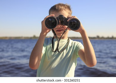 watching through binoculars. Boy looks through binoculars at the river, the position of a full-face