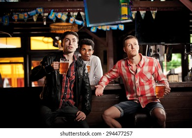 Watching TV in bar. happy young men drinking beer and gesturing while sitting in bar
