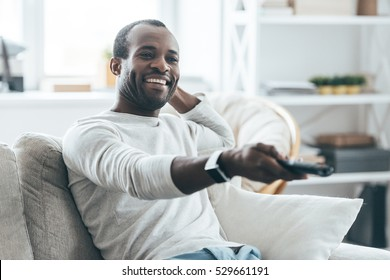 Watching TV at home. Handsome young African man watching TV and smiling while sitting on the sofa at home