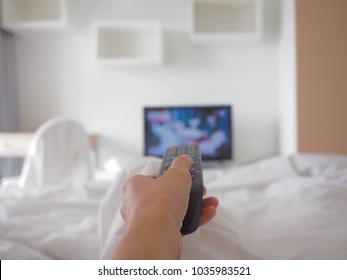 Watching tv and using remote control, Hand holding tv remote control and surfing programs on television. Watching TV in the living room or bedroom. copy space.