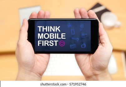 Watching two hand holding mobile phone with Think mobile first word and feature icon with blur desk office background,Digital marketing.