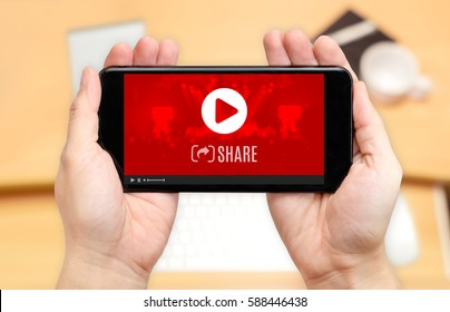 Watching two hand holding mobile phone with play and share video icon on screen and blur desk office background,Digital content concept