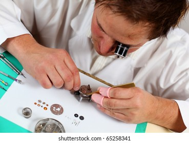 Watchmaker in his workshop repairing a wrist watch. Intentional shallow depth of field, focus on the movement.