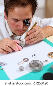 Watchmaker in his workshop repairing a wrist watch. Intentional shallow depth of field, focus on the eye.