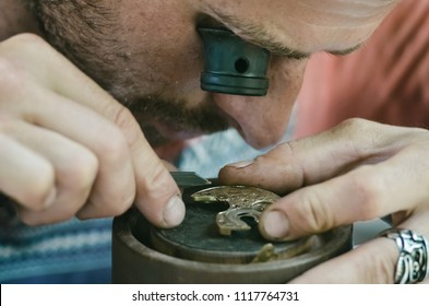 The watchmaker is a jeweler with a magnifying glass - a monocle engraves the details of the mechanism of antique gold watches in his workshop.