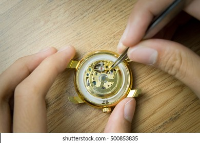 Watchmaker repairing watch on his table.