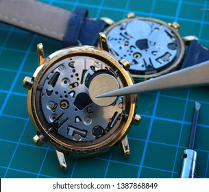 watchmaker replacing watch battery, close up of battery and quartz watch caliber