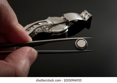watchmaker is working to replace the battery on an old quartz metal watch in his repair shop, he is holding the new battery in tweezers and getting ready to service the watch on dark black background
