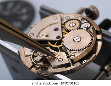 watchmaker working with tweezers into vintage mechanic watch movement