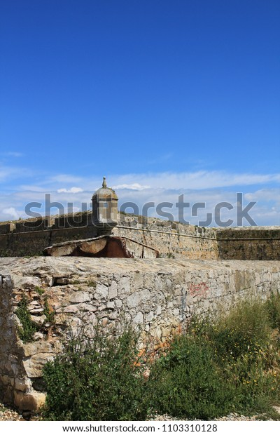 Watchtower of the fortress on the beach in Peniche village, Portugal, under blue sky in Spring