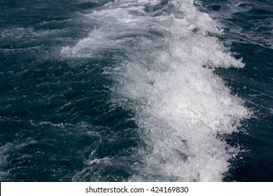 Wate waves are being formed behind a boat.