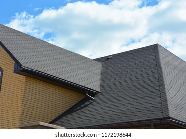 Wateproofing roof problem area with asphalt shingles and rain gutter. Asphalt shingles roofing construction.