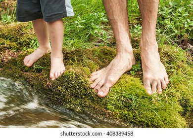 Water adventure - Close up image of father and son's feet stepping in a river