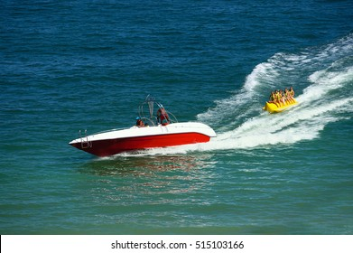 Water amusement on banana boat. summer holiday by the sea. Beautiful bright blue water and red and white boat and yellow banana boat.