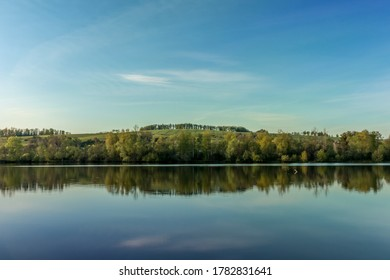 Water area of the pond with perfect reflection during a sunny morning. - Shutterstock ID 1782831641