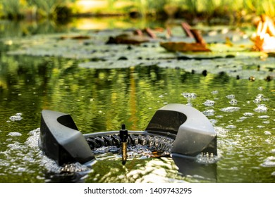 Water around skimmer boils from air bubbles. Blurred background. Skimmer floats on surface of water and collects leaves, dirt from surface.  Selective focus. Plants are reflected in purified water.
