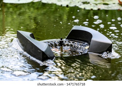 Water around skimmer boils from air bubbles. Very close-up. Skimmer floats on surface of water and collects leaves, dirt and other foreign objects from surface. Plants are reflected in purified water.