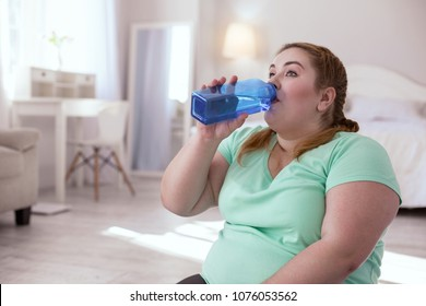 Water balance. Overweight young woman sitting on the yoga mat while drinking water from the bottle