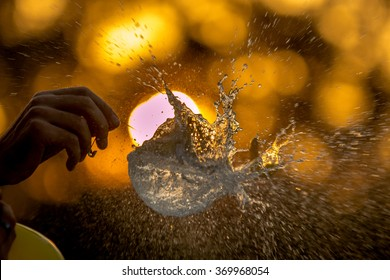 Water Balloon burst against a sunset background, creating an explosion of water droplets