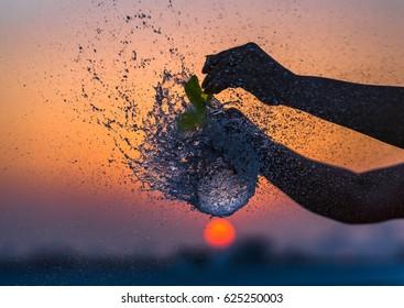 A water balloon bursting against an orange sky.