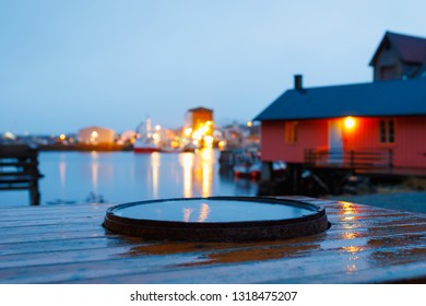 water in barrel with typical red house in background