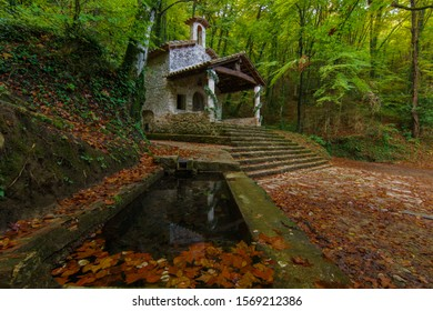 Water basin ans nice church in an autumn forest