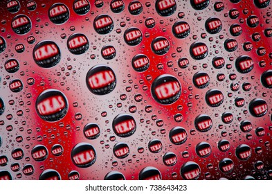 Water beads on glass with coloured background