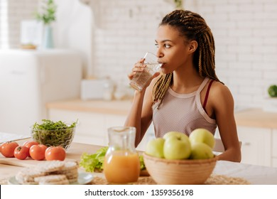 Water before breakfast. Slim and fit woman with many little braids drinking water before having breakfast