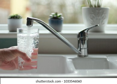 Water being poured into glass from kitchen tap - Shutterstock ID 1033546060