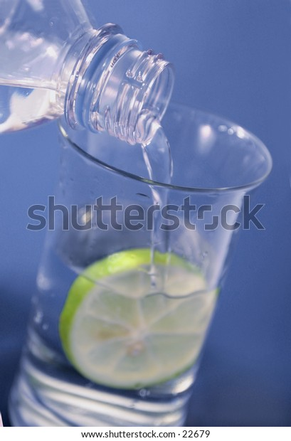 water being poured,a slice of lime in the glass