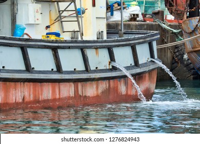 water being pumped from a fishing vessel while being moored to the quay