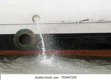 Water being pumped out the side of a small boat. A porthole is below and to the left of the pump hole.